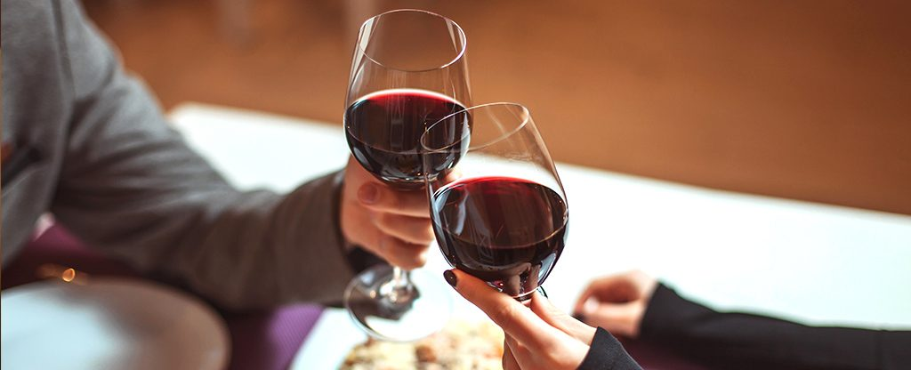Couple Toasting Red Wine on Labor Day Weekend Getaway