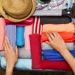 Woman packing suitcase full of clothes for summer vacation.